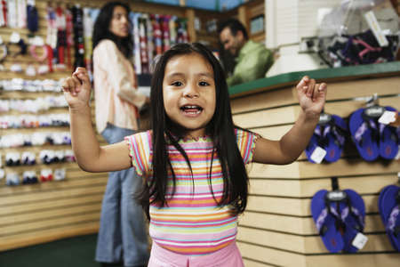 shopping buddies: Young Hispanic girl cheering at shoe store, Port Washington, New York, United States LANG_EVOIMAGES