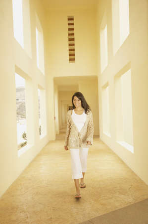 approaching: Woman walking down sunlit hallway, Los Cabos, Mexico LANG_EVOIMAGES