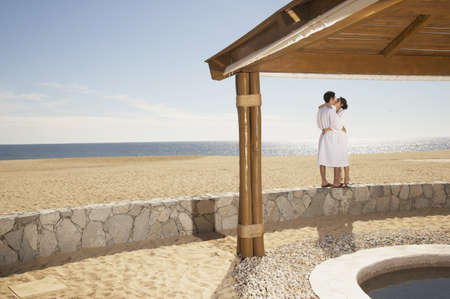 los cabos: Couple in bathrobes kissing at beach, Los Cabos, Mexico LANG_EVOIMAGES