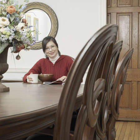 america's cup america: Asian woman eating and reading at dining table