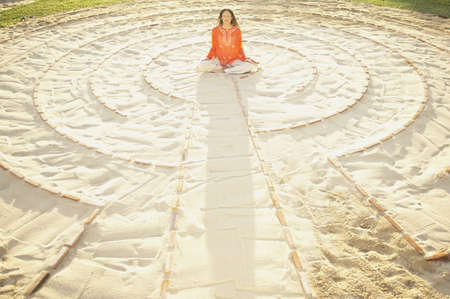 longshot: Woman sitting cross-legged in the middle of a meditation labyrinth