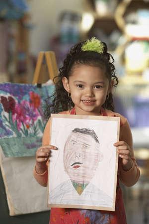 artwork: Young Hispanic girl holding artwork LANG_EVOIMAGES