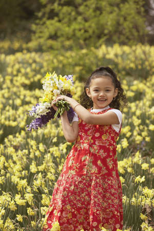 thespian: Young Hispanic girl holding picked flowers outdoors LANG_EVOIMAGES