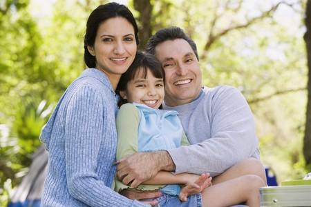Hispanic family hugging outdoors