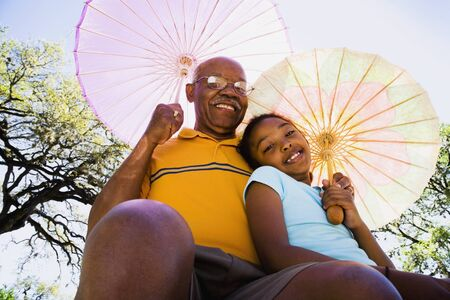 parasols: African American grandfather and granddaughter with parasols