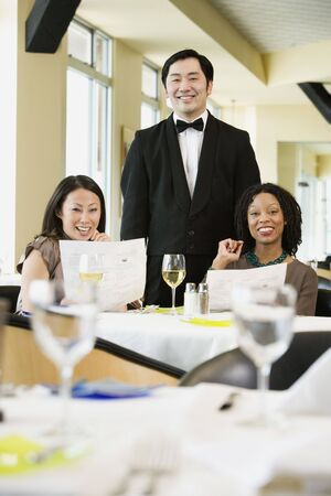 solicitous: Two women with waiter in restaurant LANG_EVOIMAGES