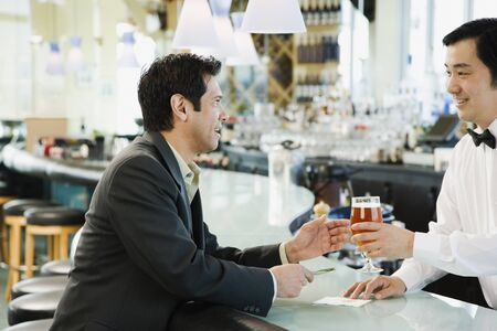 barkeep: Male bartender serving man drink at bar LANG_EVOIMAGES