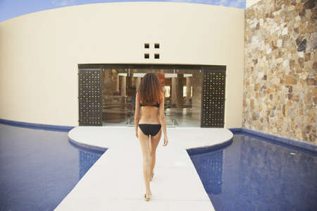 stepping: Woman walking next to resort hotel pool, Los Cabos, Mexico