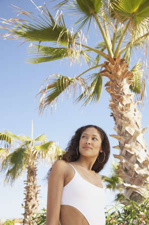 Hispanic woman in bathing suit next to palm trees, Los Cabos, Mexico Stock Photo