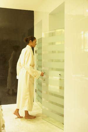 bathtowel: Woman in bathrobe entering spa shower