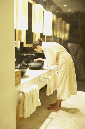 bathtowel: Woman washing her face in spa bathroom