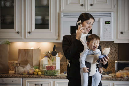 talker: Hispanic mother on cell phone with baby in front pack LANG_EVOIMAGES