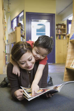 Mother and young son reading book at bookstore