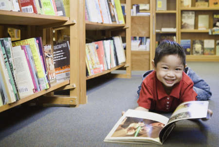 babyboomer: Young boy smiling at bookstore LANG_EVOIMAGES