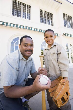 mid life: African American father and son with baseball equipment