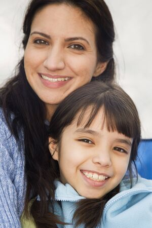 fathering: Hispanic mother and daughter smiling