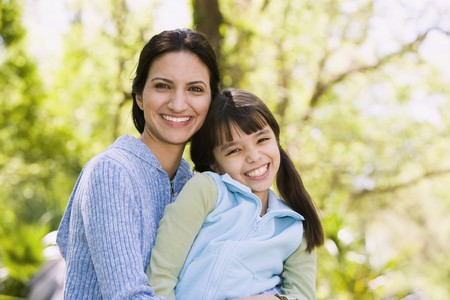 poppa: Hispanic mother and daughter smiling outdoors LANG_EVOIMAGES