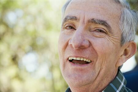 leaning by barrier: Close up of senior Hispanic man laughing