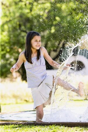 spattering: Young Hispanic girl playing in water outdoors