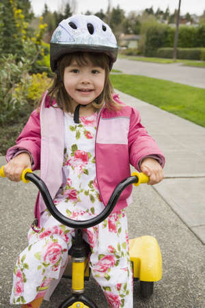 motorcoach: Young Asian girl with helmet riding tricycle