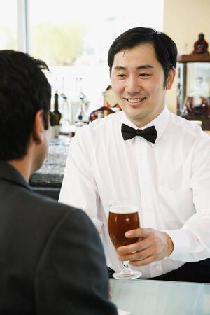 barkeep: Asian male bartender serving man drink at bar LANG_EVOIMAGES