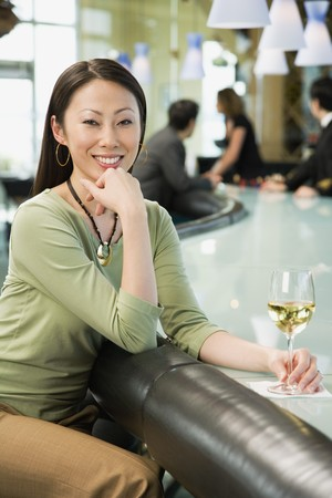 bestowing: Woman at bar with glass of wine LANG_EVOIMAGES