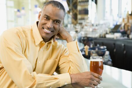bar: African American man with drink at bar LANG_EVOIMAGES
