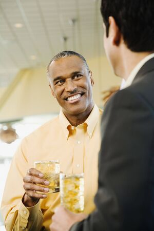 African American man with drink talking to friend