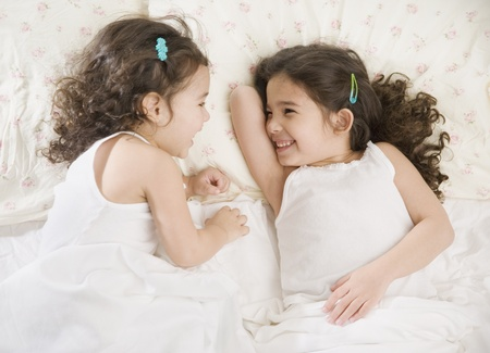 giggling: Two young Hispanic sisters giggling in bed