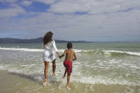 south american ethnicity: African mother and son running in the surf, Florianopolis, Brazil LANG_EVOIMAGES