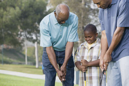 adult boys: African American family playing golf