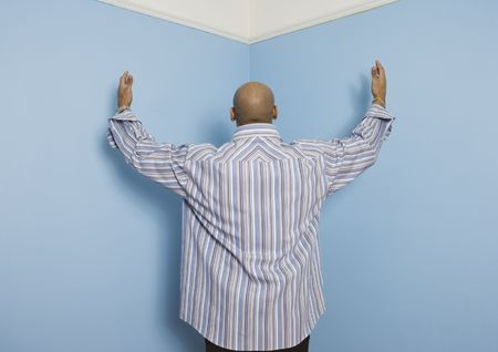 casualness: Rear view of African American man facing corner with arms raised