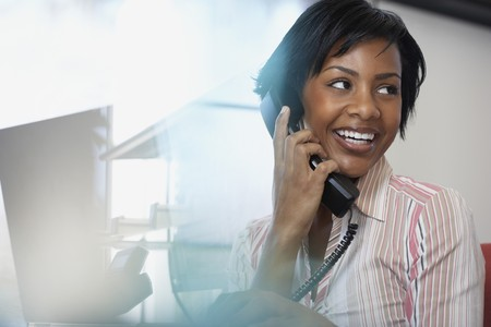 landline: African American businesswoman talking on telephone LANG_EVOIMAGES