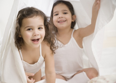 bedcover: Two young Hispanic sisters playing under sheet