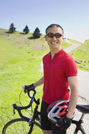 Asian man with bicycle outdoors Stock Photo