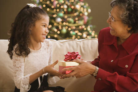 Hispanic grandmother giving granddaughter Christmas gift