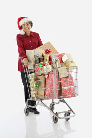 woman shopping cart: Senior Hispanic woman with shopping cart full of gifts