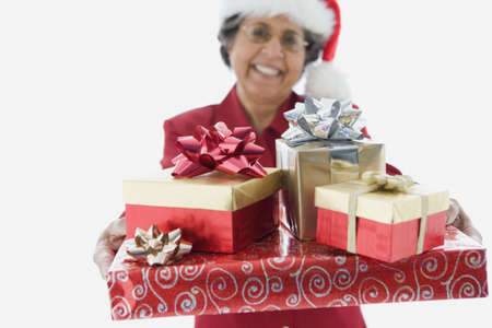 bestowing: Senior Hispanic woman holding stack of gifts