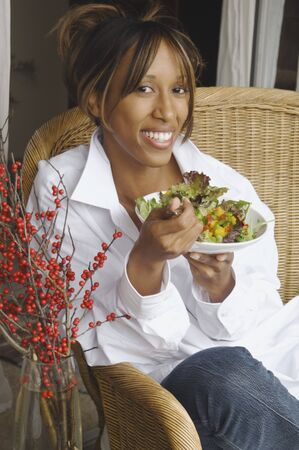 casualness: African American woman eating salad