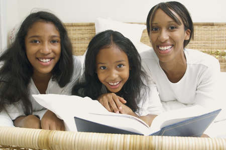 casualness: African American mother and daughters on bed with book
