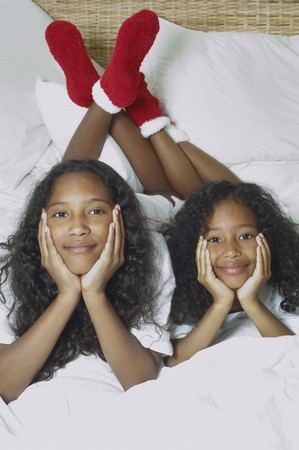 casualness: Two African American sisters on bed
