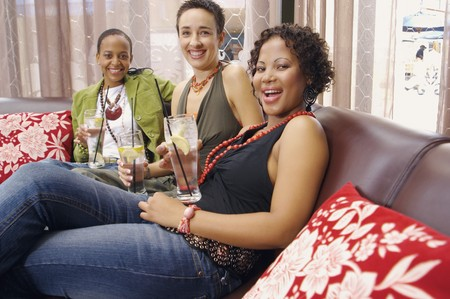 davenport: Three women smiling and drinking on sofa