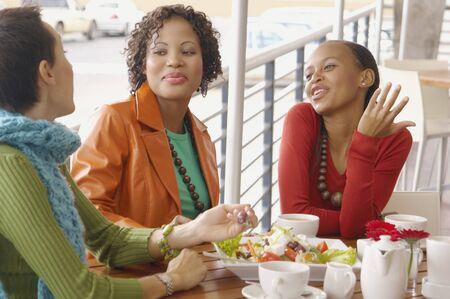 women talking: Three women eating and talking