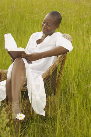front raise: African American woman reading book outdoors LANG_EVOIMAGES