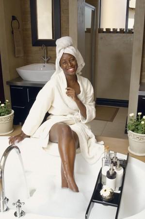 woman in bath: African American woman in bathrobe drawing a bath