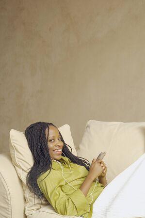 davenport: African American woman with MP3 player on sofa