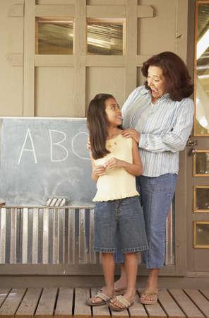 schoolroom: Hispanic female teacher with female student