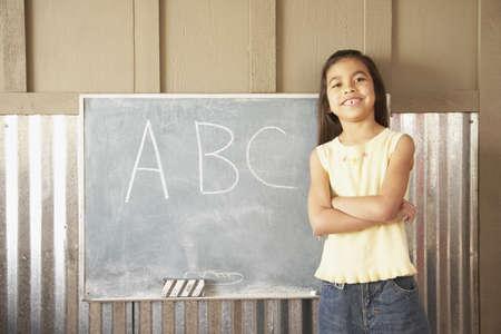 gramma: Hispanic girl standing in front of blackboard LANG_EVOIMAGES