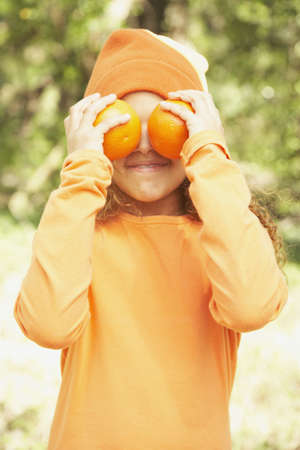 babyboomer: African American girl holding oranges over her eyes LANG_EVOIMAGES