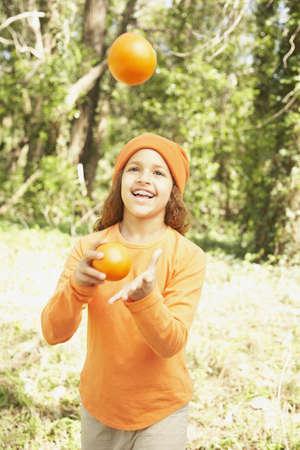 mischeif: African American girl juggling oranges LANG_EVOIMAGES